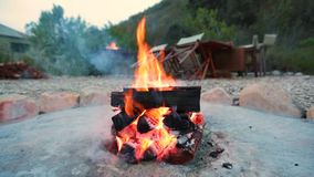 A campfire burns in a fire pit at a safari camp stock video footage