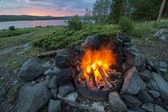 A campfire burns hot at a lakeshore campsite, as the sun sets in the mountains. Stock Photography