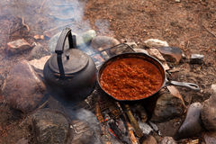 Campfire Cooking. Cooking Dinner on campfire in cast iron pan Stock Image