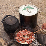 Campfire Cooking. Cooking Dinner on campfire in cast iron pan Stock Photo