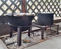 Campfire Cooking Boilers. Two large boilers stand on a special fire stand stock photo