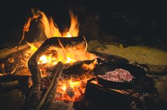 Campfire cooking meat in skillet Royalty Free Stock Photography