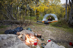 Campfire With Couple Relaxing In Tent At Forest Stock Image