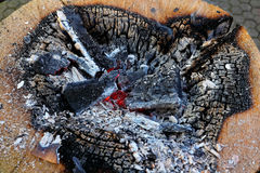Campfire embers. Topview shot of a campfire going out which was lighted in a tree trunk. Christmas season Royalty Free Stock Photo