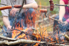 Campfire fire Flames grilling sausage on the BBQ Stock Image