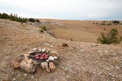 Campfire firepiit with moose hamburgers on it in the Pryor mountains in Montana. United States Royalty Free Stock Images