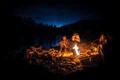 Campfire with friends. Campfire by the river with friends after a hike in a national park. People having good time together stock photo