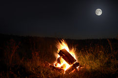 Campfire with full  moon Stock Images