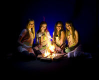 Campfire Girls. Four beautiful teenage girls with aprons and cooking gloves sitting around a campfire royalty free stock image