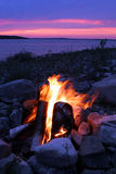 Campfire On The Lake. A campfire roars as the sun goes down Royalty Free Stock Photo