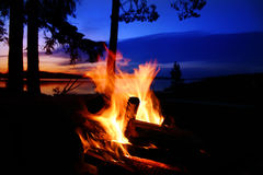 Campfire by a lake. At sunset stock image