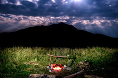 Campfire near mountain at night Royalty Free Stock Photo