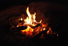 Campfire at night. Featuring small wood logs and burning embers stock images