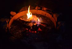 Campfire in At Night-with Hot Orange Embers. Campfire in a Fire Ring surrounded by Stones Royalty Free Stock Photo