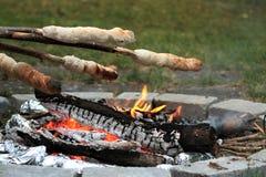 Campfire- och brödbakning med sticken arkivbilder