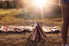 Campfire On Green Grass, Plaid Lies Near, Beautiful Nature, Calm Atmosphere, Sunshine, No People On Photo. Summer Vacation, Picnic Royalty Free Stock Images