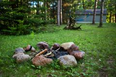 Campfire pit on green lawn with a hammock hanging in the background - 1/2 stock image