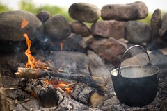 Campfire and pot. A metal cooking pot beside a burning campsite fire inside a stone ring fireplace Stock Photos