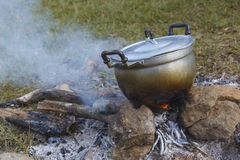 Campfire pot boiling. Preparing food on campfire in wild camping Stock Photo