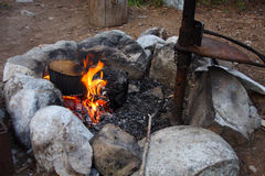 Campfire Ring. Burning campfire with grill surrounded by rocks royalty free stock image