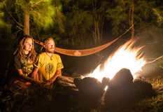 Campfire on a rocky beach with couple sitting. Campfire on a rocky beach with a couple  sitting Royalty Free Stock Image