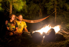 Campfire on a rocky beach with couple sitting Royalty Free Stock Image