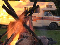 Campfire with RV in background. In park royalty free stock photo