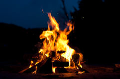 Campfire with Shooting Sparks. A campfire by a lake with sparks rising into the night Royalty Free Stock Photo