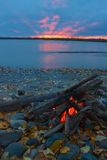 Campfire on the shore of Talkeetna river. Lit campfire on the shore of Talkeetna river with red sunset stock photography