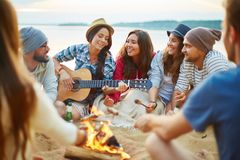Campfire singing. Friendly girls and guys singing by guitar by campfire royalty free stock images