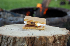 Campfire smores. A s'more on a wooden stump with a campfire on the background stock photo
