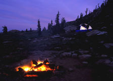 Campfire with tent. Campfire with glowing tent at dusk stock images