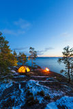 Campfire and tent in wilderness by the lakeside Royalty Free Stock Image
