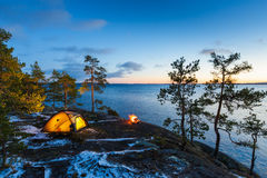Campfire and tent in wilderness by the lakeside Stock Photos