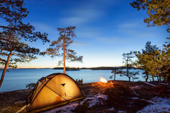 Campfire and tent in wilderness by the lakeside Stock Image