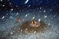 Campfire under falling snow. Campfire and snowfall at night Royalty Free Stock Photos