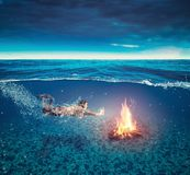 Campfire underwater. Young woman swims underwater royalty free stock image