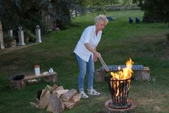 For the campfire, the young woman puts firewood on the fire basket royalty free stock photos