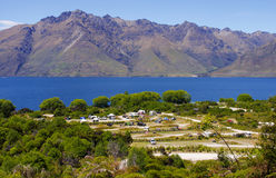 Campground by mountains and blue lake. Twelve Mile Delta Campgroud along the blue waters of Lake Wakatipu with mountains in the background Stock Photos