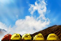 Campground in the mountains. Many yellow adn red tents against the blue sky with amazing clouds.  Royalty Free Stock Photos