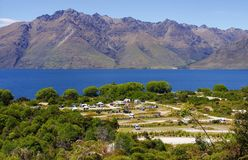 Campground by vibrant mountain lake. Campground along Lake Wakatipu in New Zealand Stock Photo