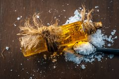 Camphor powder in a small spoon along with its essential oil in a glass bottle with it on wooden surface. Aurvedic herb camphor powder in a small spoon and its royalty free stock photo