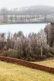 Campi collinosi gelidi di vista della campagna con gli alberi Fotografia Stock