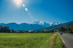Campi con le case e strada, foresta, paesaggio alpino e cielo blu in San-Gervais-Les-Bains Immagini Stock