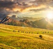 Campi rurali vicino alle alte montagne al tramonto Fotografia Stock