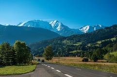 Campi, strada, foresta, paesaggio alpino e cielo blu in San-Gervais-Les-Bains Immagine Stock Libera da Diritti