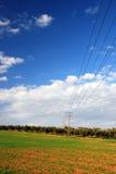 Campi verdi, cielo blu, linee elettriche Fotografia Stock