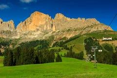 Campi verdi e alte montagne, dolomia, Italia Fotografia Stock