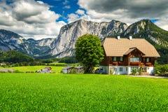 Campi verdi fantastici con le case e le montagne alpine, Altaussee, Austria Fotografie Stock