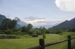 Campi verdi nelle alpi, Italia Bella vista sull'alpi italiane Cielo blu Fotografia Stock